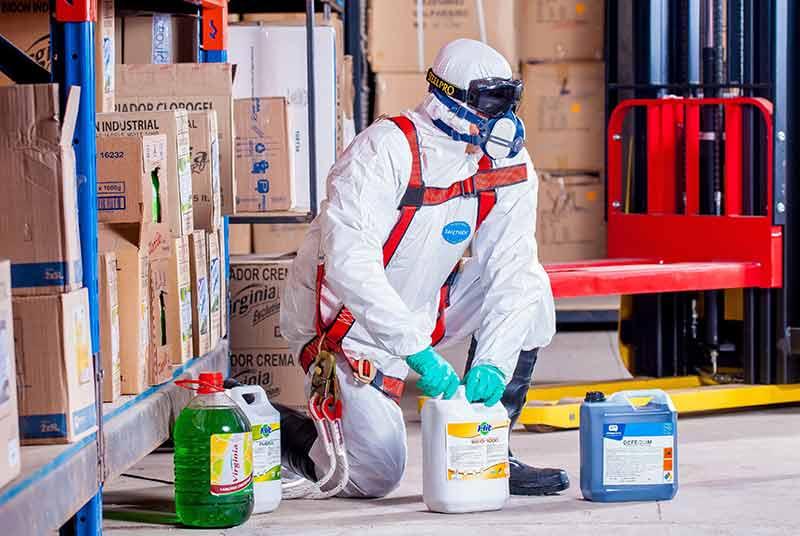 Hombre agachado con traje especial y productos de limpieza