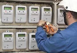 Electricista manipulando con unos alicates un cuadro de contadores centralizado por Rojeque reformas en Sevilla.