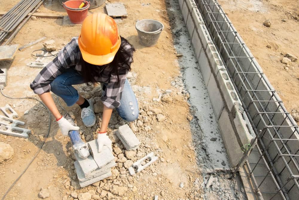 Una trabajadora de Rojeque cortando ladrillos para la construcción de una vivienda